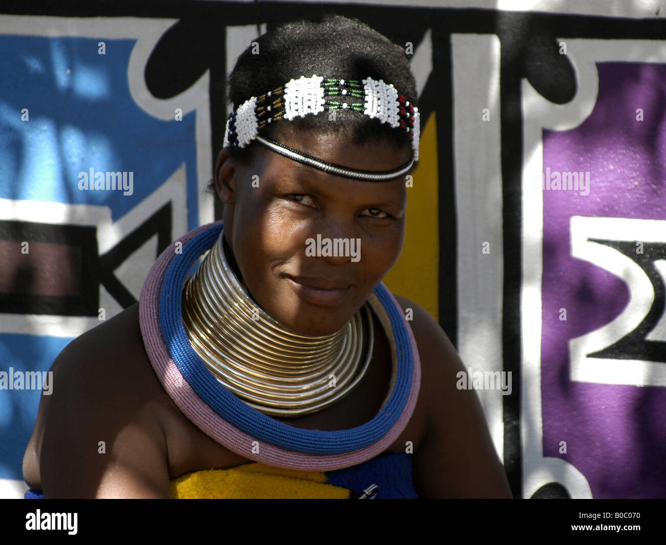 A Ndebele woman in their traditional clothing in the museum village of Botshabelo in South Africa near Middelburg. - Stock Image