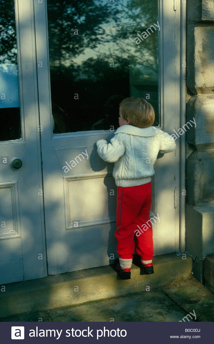 Young boy, toddler, on tiptoes peering through a window. - Stock Image
