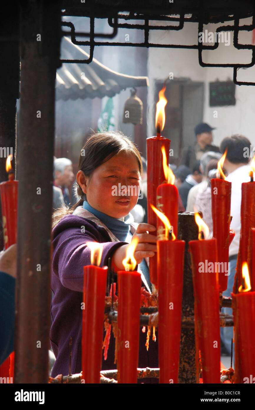 A Chinese  Buddhist woman lighting  candles  at the Hanshan or Cold Mountain Temple near Suzhou.China. - Stock Image
