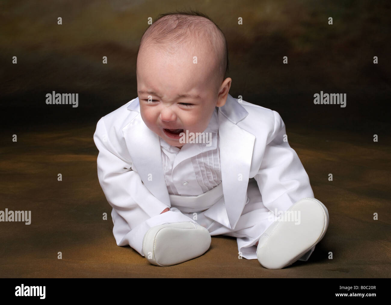 little biracial baby boy sitting in white tuxedo crying - Stock Image
