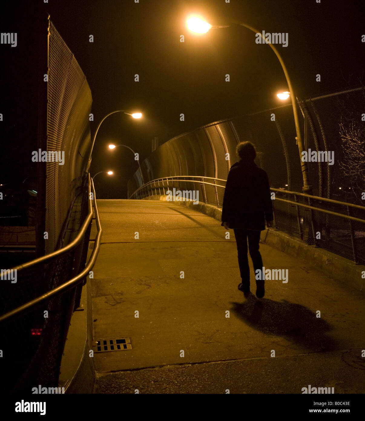 Young woman walks over pedestrian bridge in Brooklyn NY at night - Stock Image