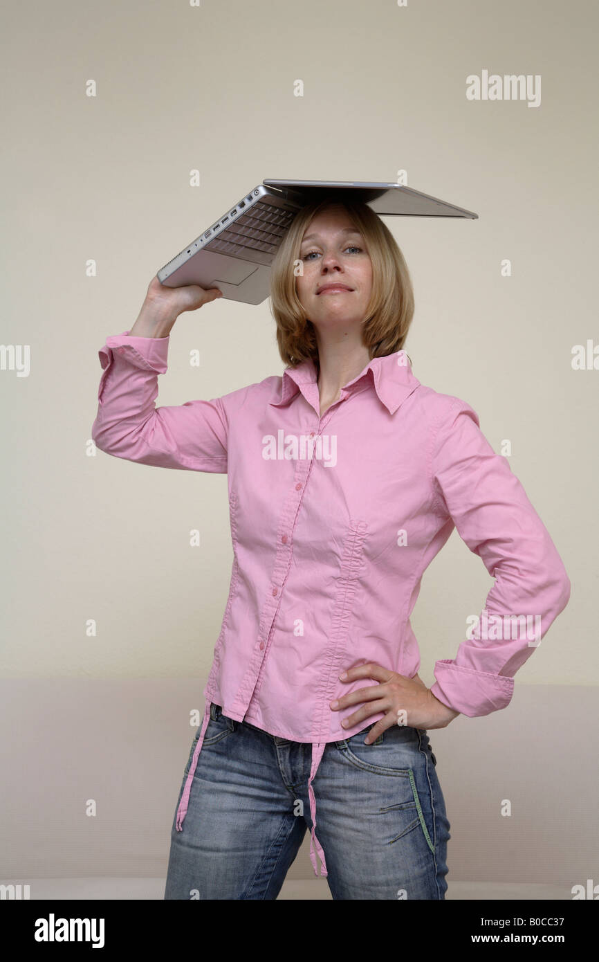 Woman holding a laptop on her head - Stock Image