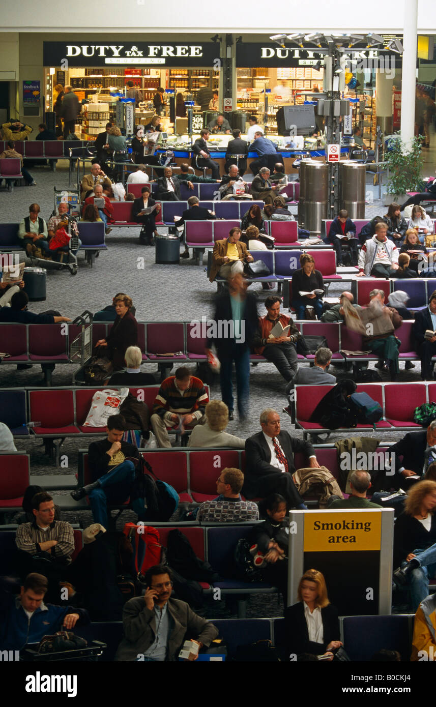 Crowds of passengers in busy Heathrow airport Terminal 4 await the call for flights patiently waiting on BAA seating Stock Photo