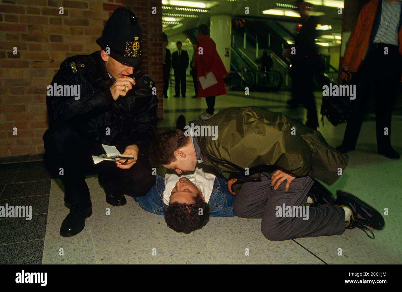 A City of London Police officer radios for medical assistance for unconscious man drunk from alcohol at Liverpool - Stock Image