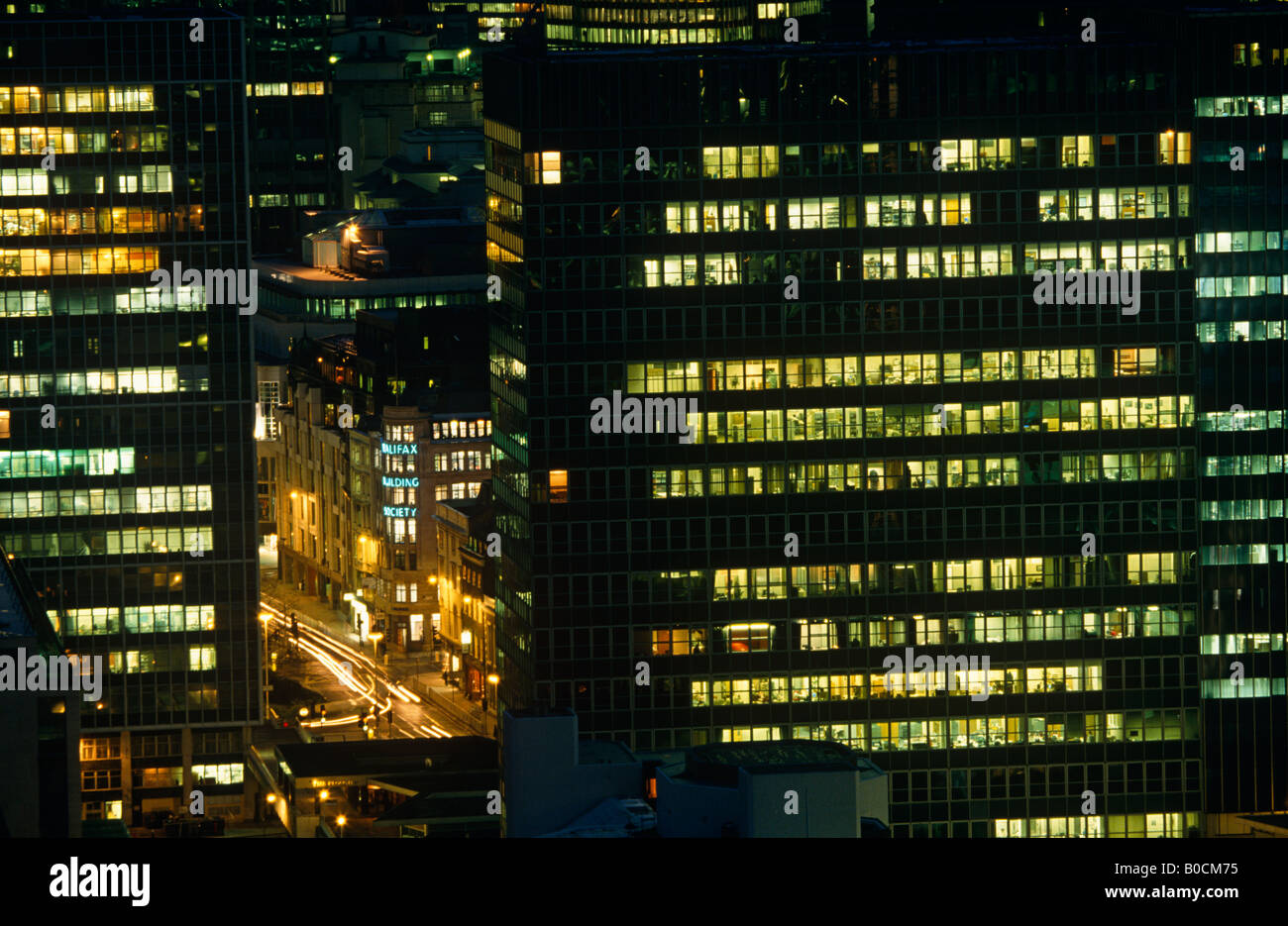 Aerial view of City of London at night, office lights glowing, traffic lights streaking through gap in building - Stock Image