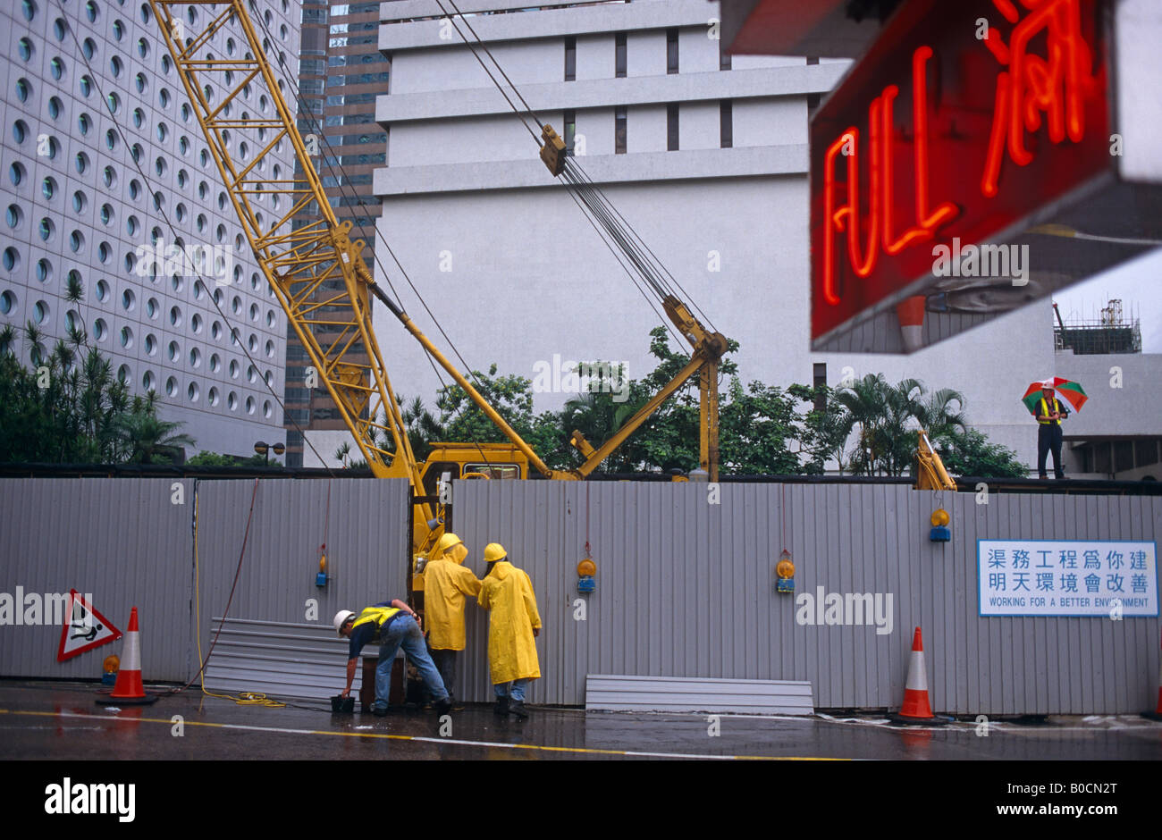 Construction workers in Central Hong Kong carry on working during a monsoonal rain shower on the last day of British - Stock Image