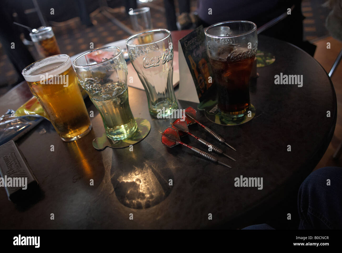 Darts belonging to an English lady player lay on a table with Coke glasses and a pint of lager beer during English - Stock Image