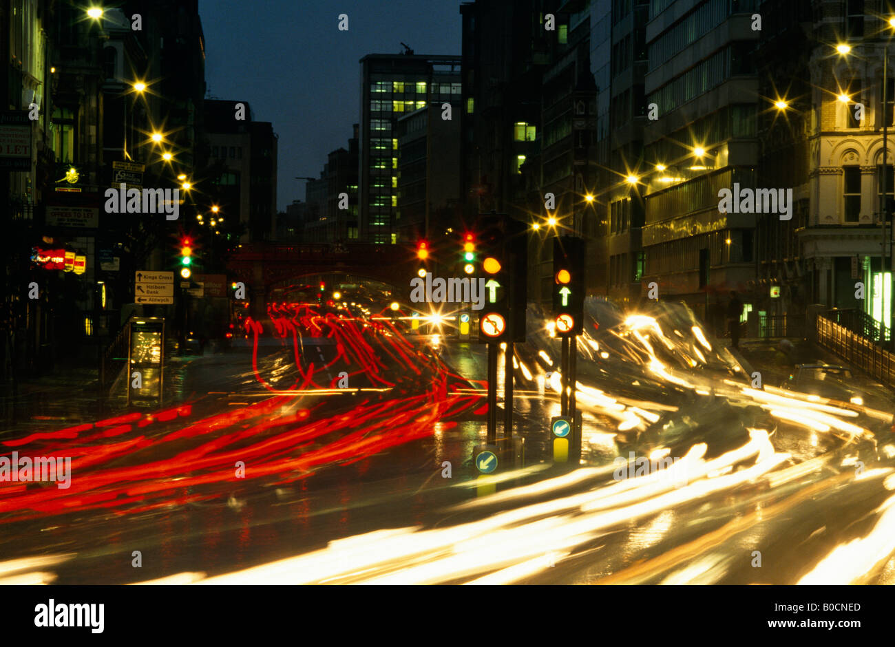 Traffic lights blurring at night over the junction of Farringdon road and Fleet Street in the City of London - Stock Image