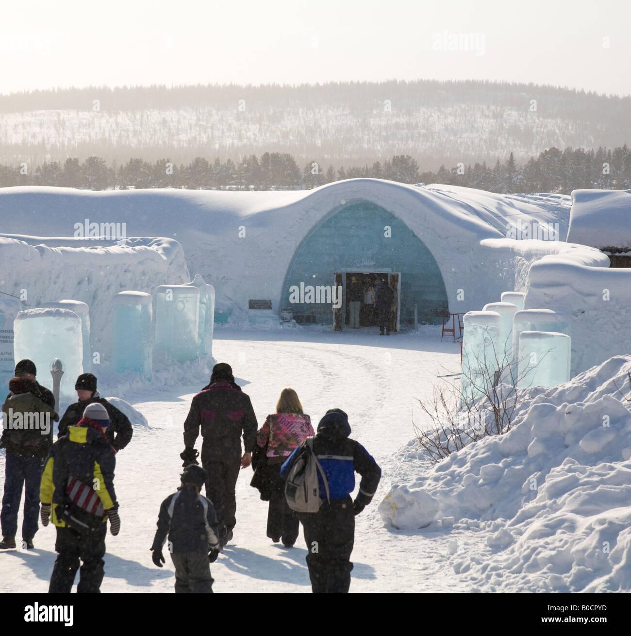Visitors walk towards the Jukkasjarvi icehotel in northern Sweden - Stock Image