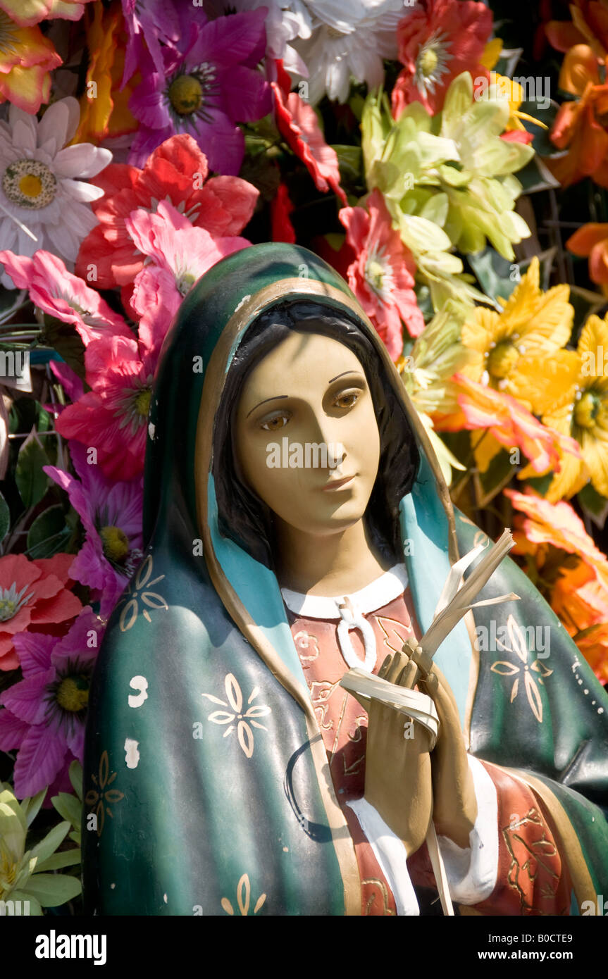 Close up of a statue of the revered Virgin of Guadalupe. Surrounded by fake flowers. Mexico City. - Stock Image