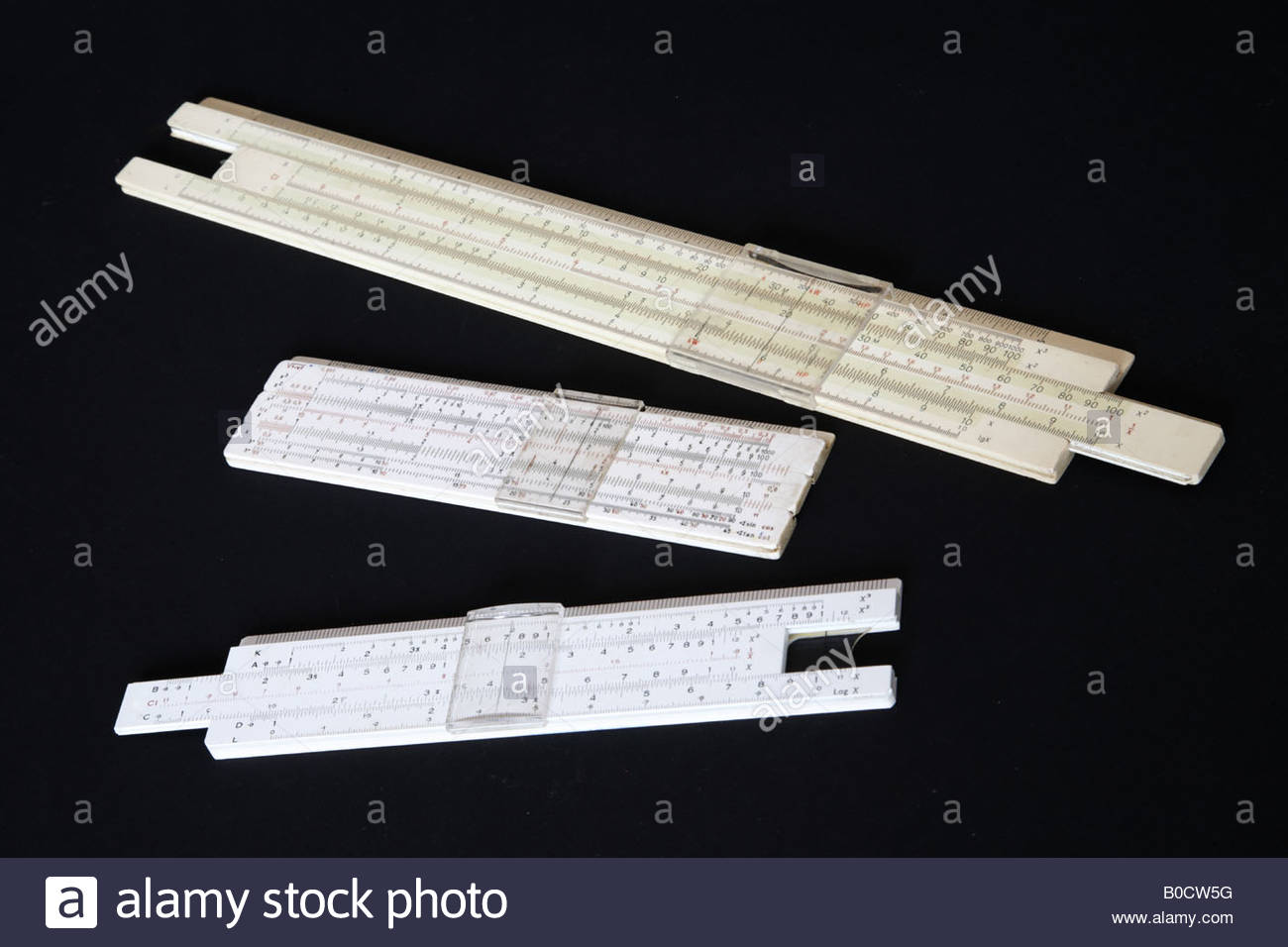 slide rulers against black background - Stock Image