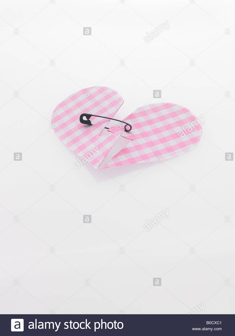 Broken heart pinned with safety pin - Stock Image