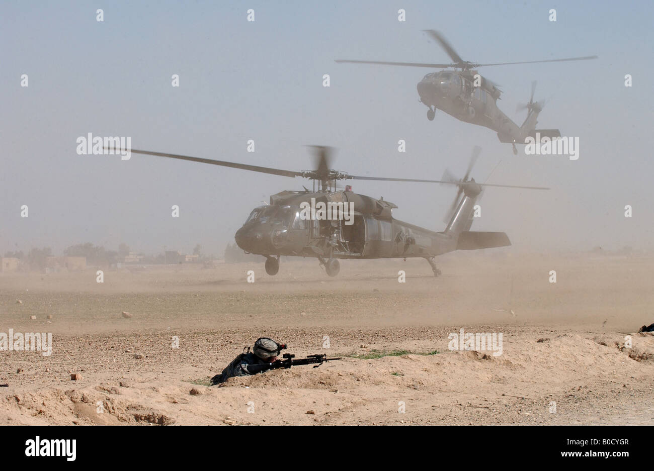 Two U S Army UH 60 Black Hawk helicopters blow up clouds a of dust as they come into a landing zone in Samarra Iraq Stock Photo