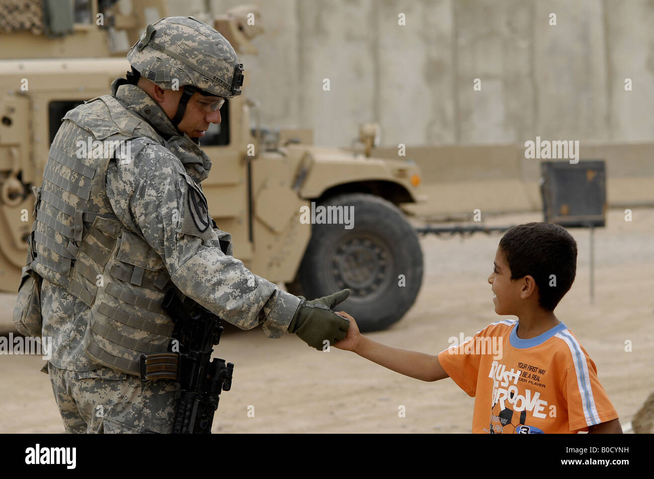 U S Army Maj Robert Rodriguez shakes hands with a local child during a visit to the market in Taji Iraq - Stock Image