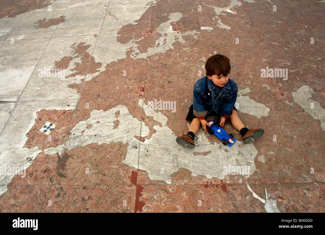 A young boy sits between Europe and Asia on a map laid across the pavement beneath the Monument of Discoveries, - Stock Image