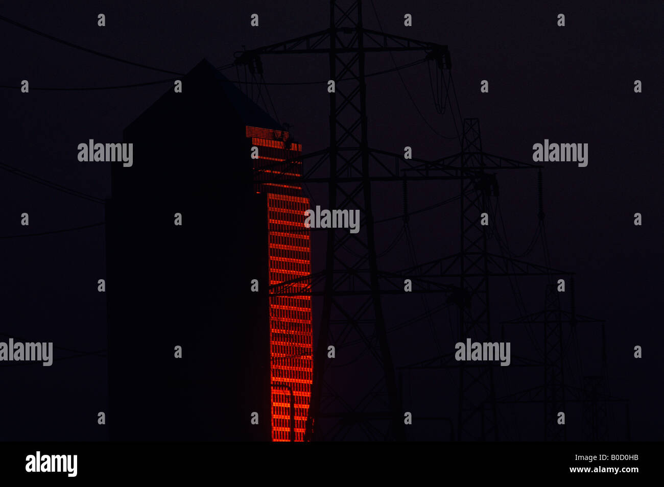 Red glowing sun reflected off the glossy façade of Canary Wharf tower next to electricity pylons - Stock Image