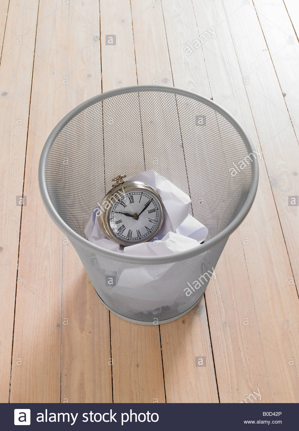 Outdated clock in trash bin - Stock Image