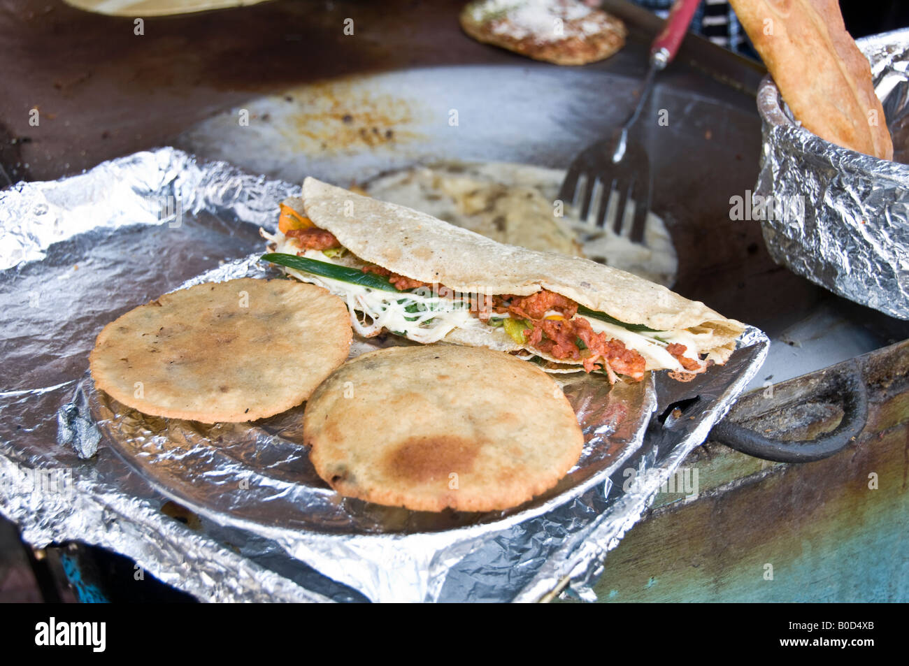 Tacos (top) and Empanadas (two at the bottom) being cooked and sold in a street market in Puebla, Mexico. Tasty, - Stock Image