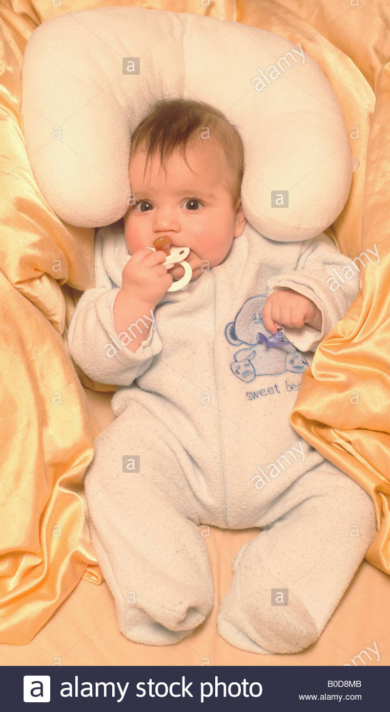 Baby in cot crib bed awake blond blonde hair baby in crib cot cute cosy blanket full length alone - Stock Image