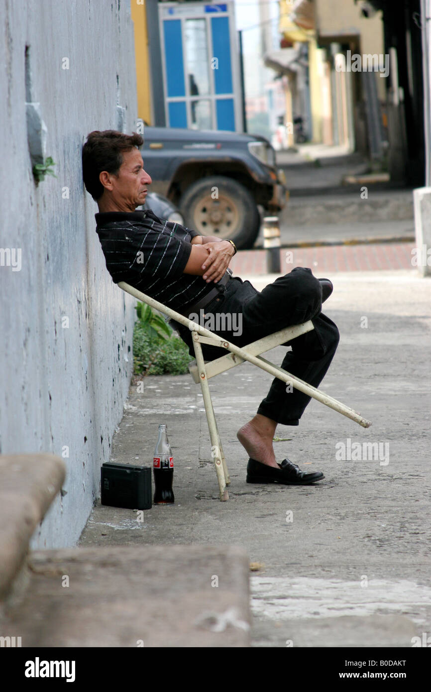 Bored man sitting against a wall in Panama City.  For Editorial use only. Stock Photo