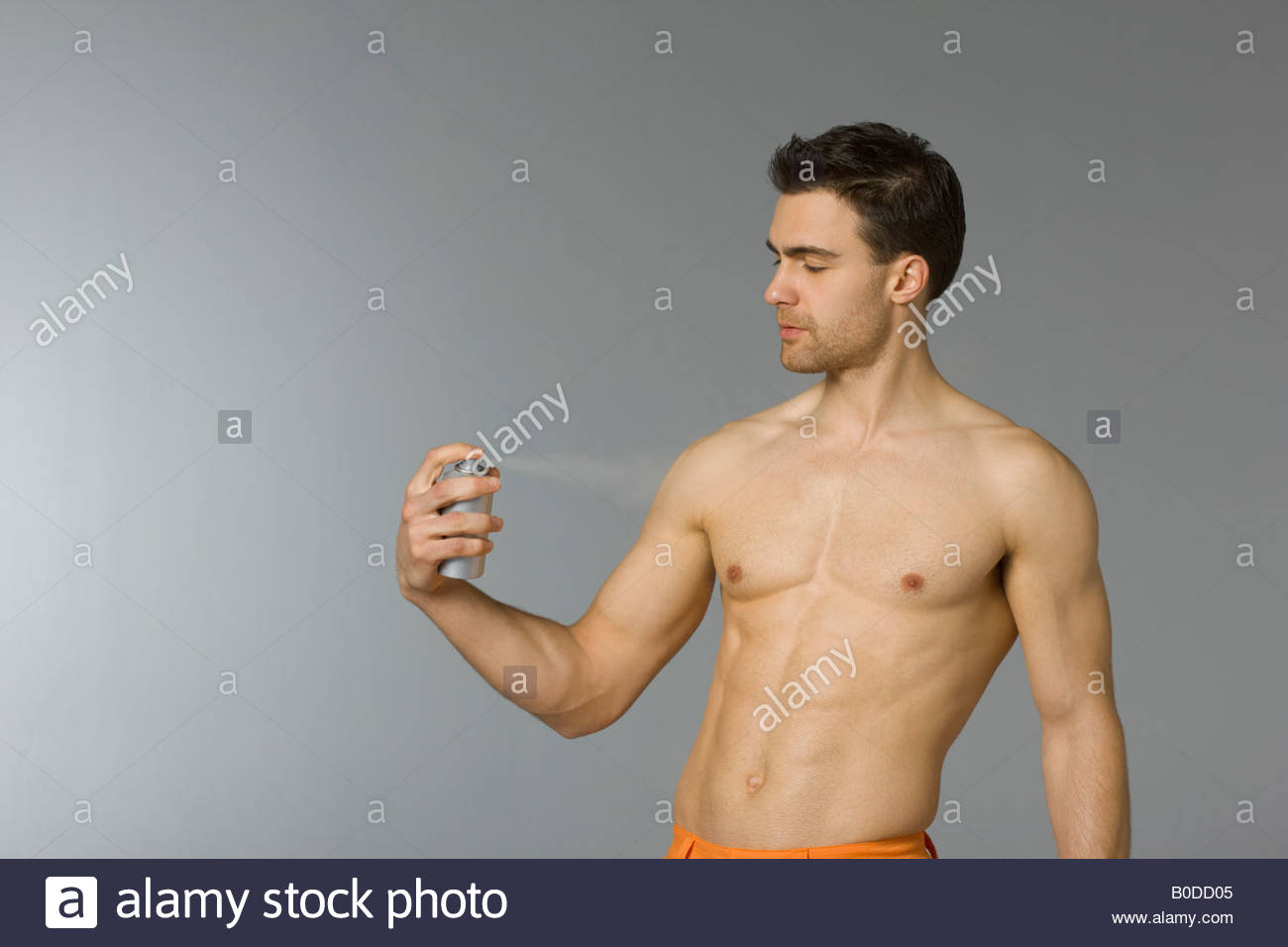 Young man spraying body deodorant - Stock Image