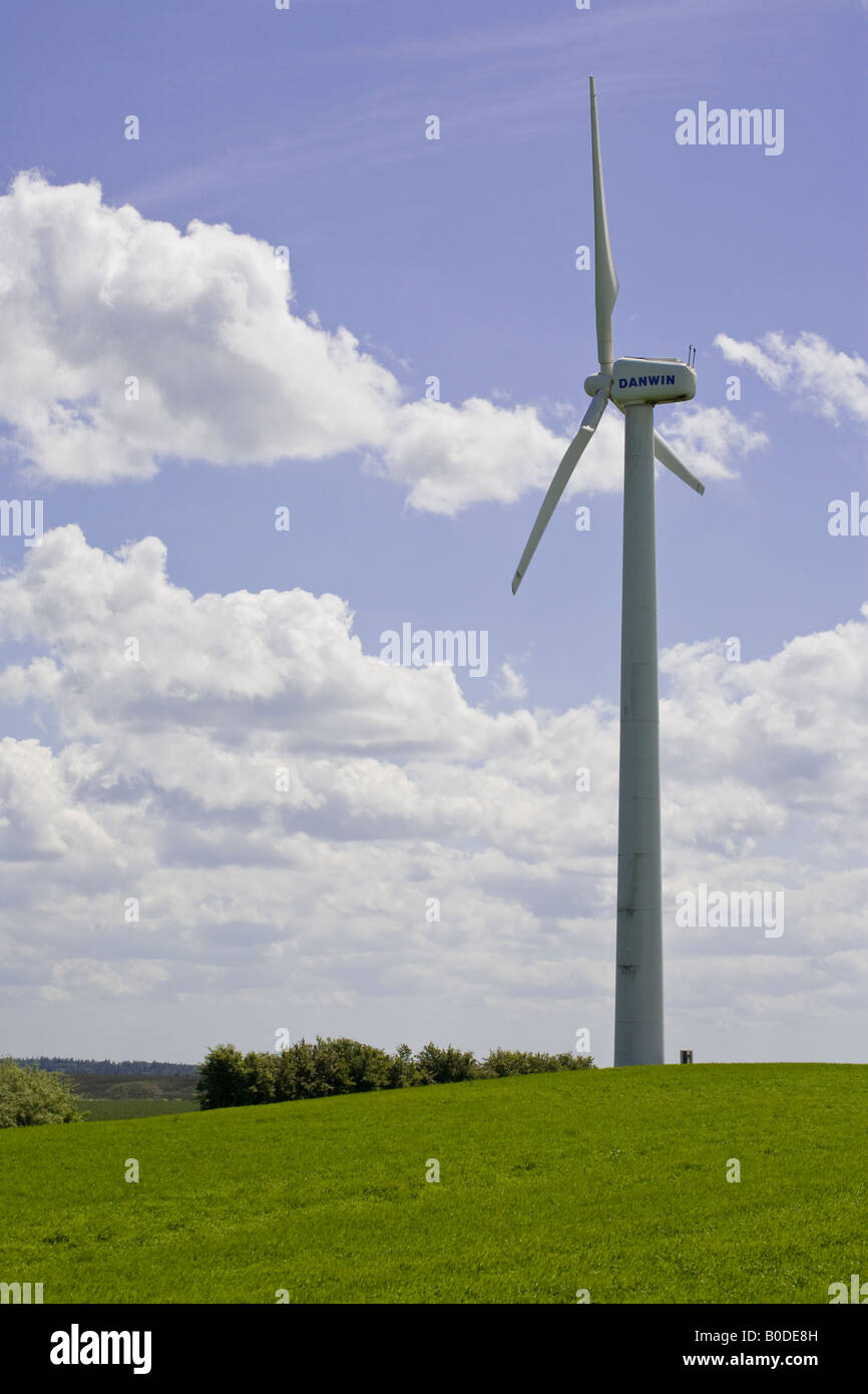 Greener Pastures A large white wind turbine sited in a rolling green grass field and a cumulus cloud sky generates - Stock Image
