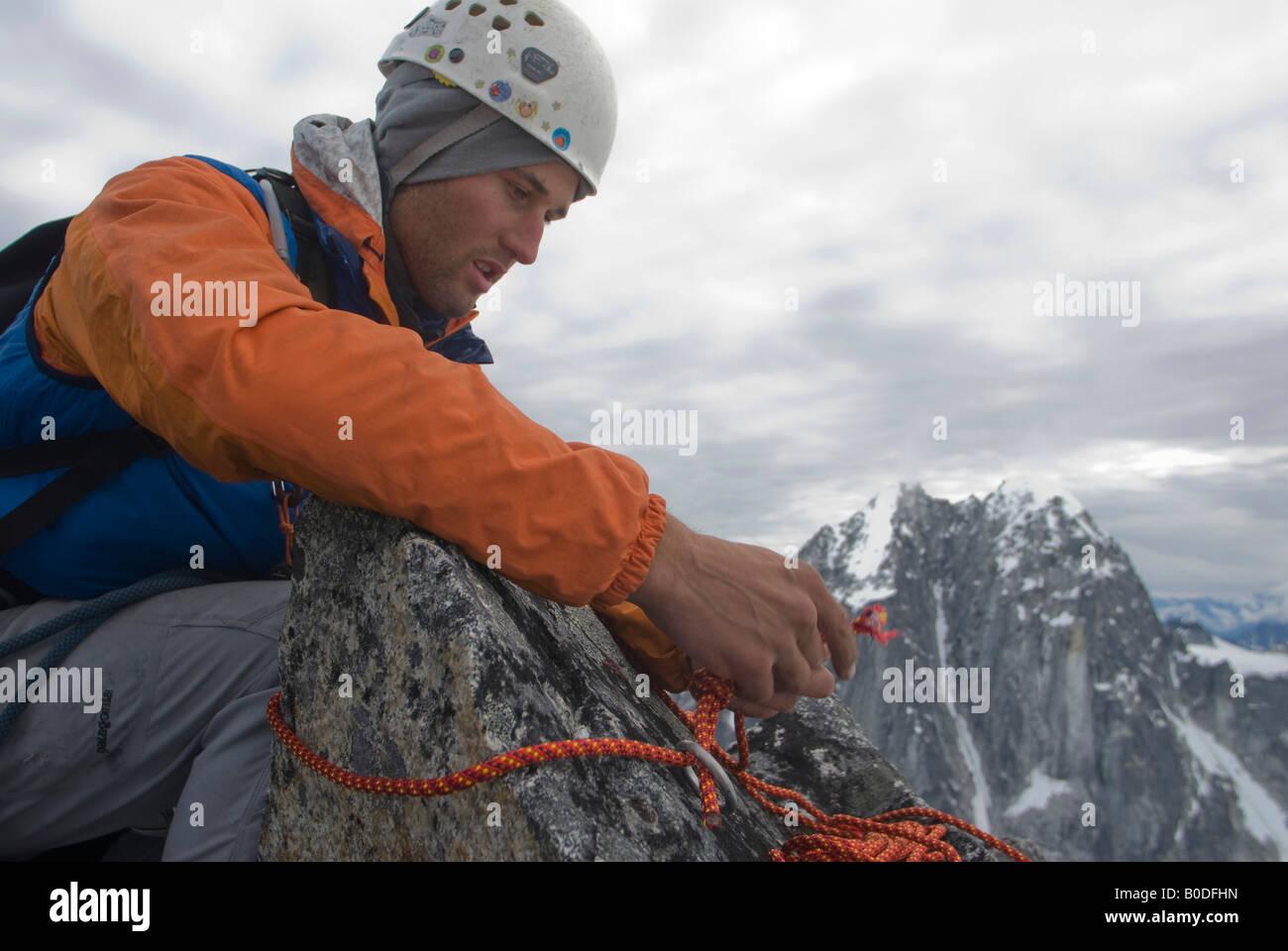 Climber building a rappel anchor on a rock horn near the