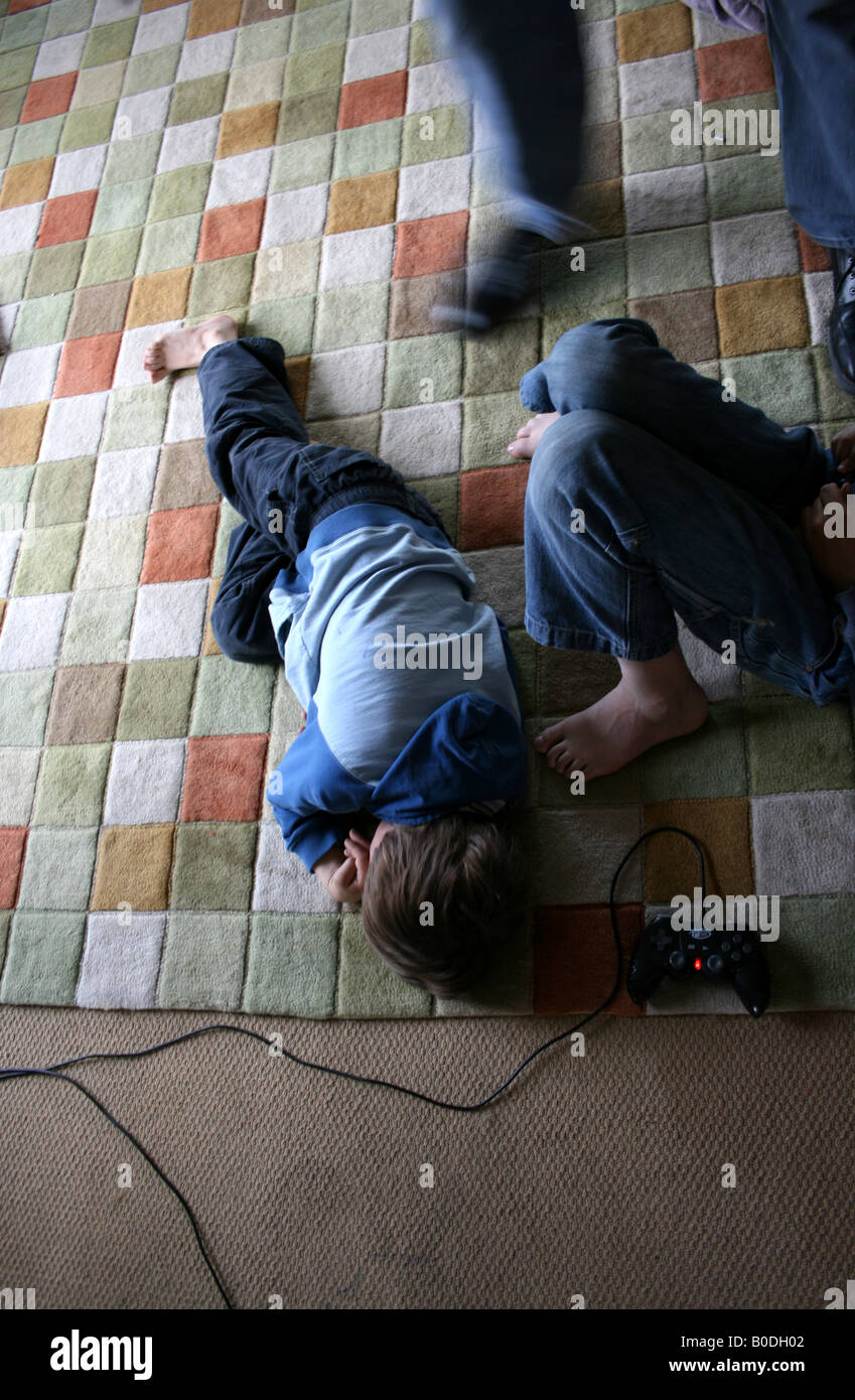 young boy lays down on floor, frustrated by video game - Stock Image