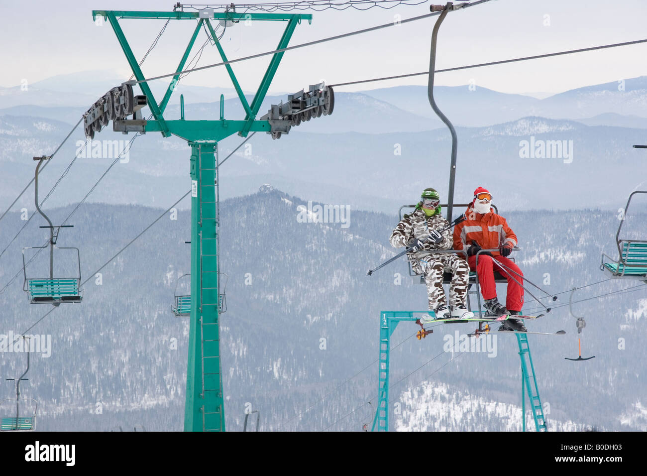 Two mountain-skiers going up the hill by cable-way - Stock Image