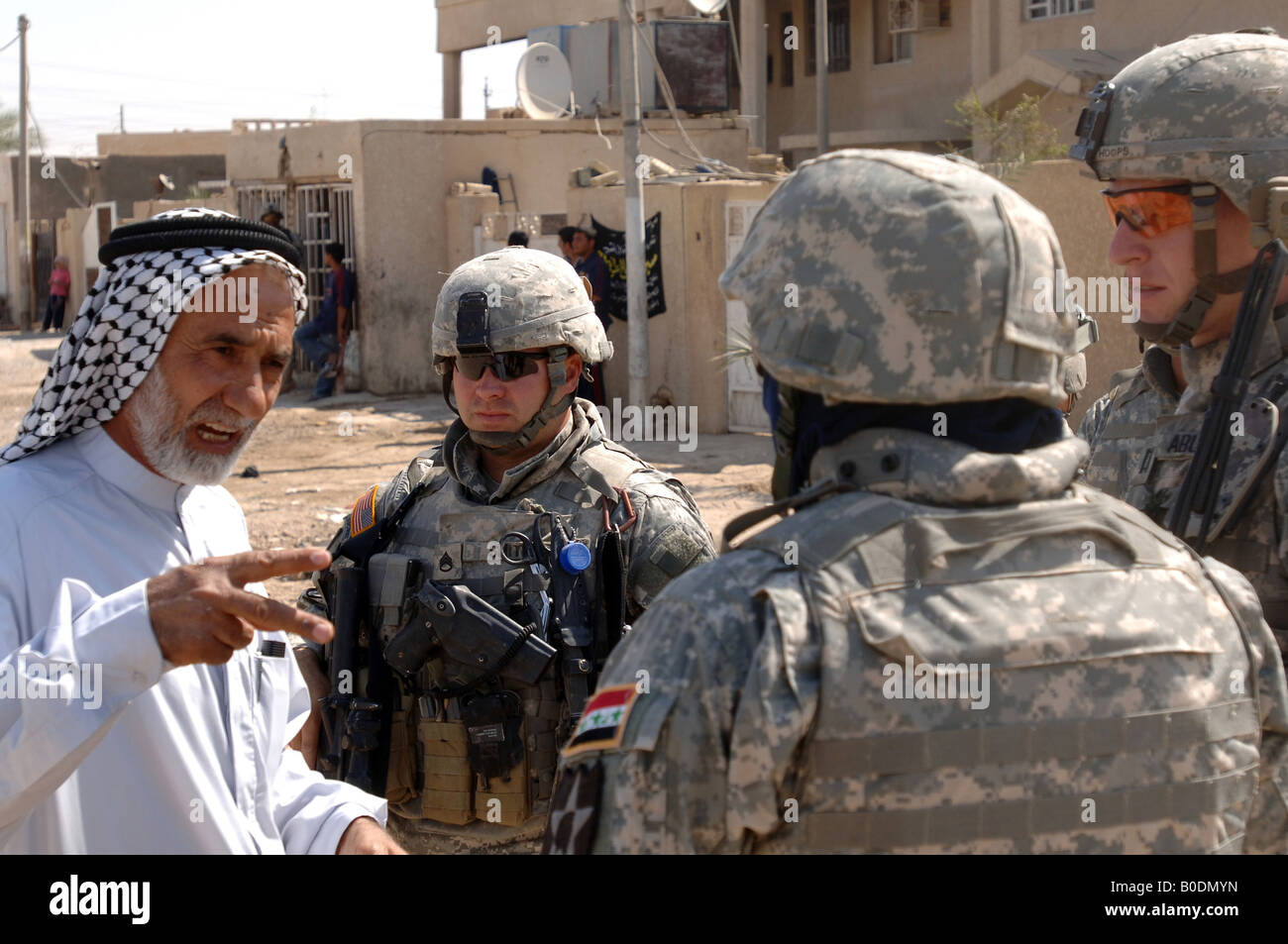 A village official explains village water supply problems to U S Army soldiers as they conduct a routine patrol - Stock Image