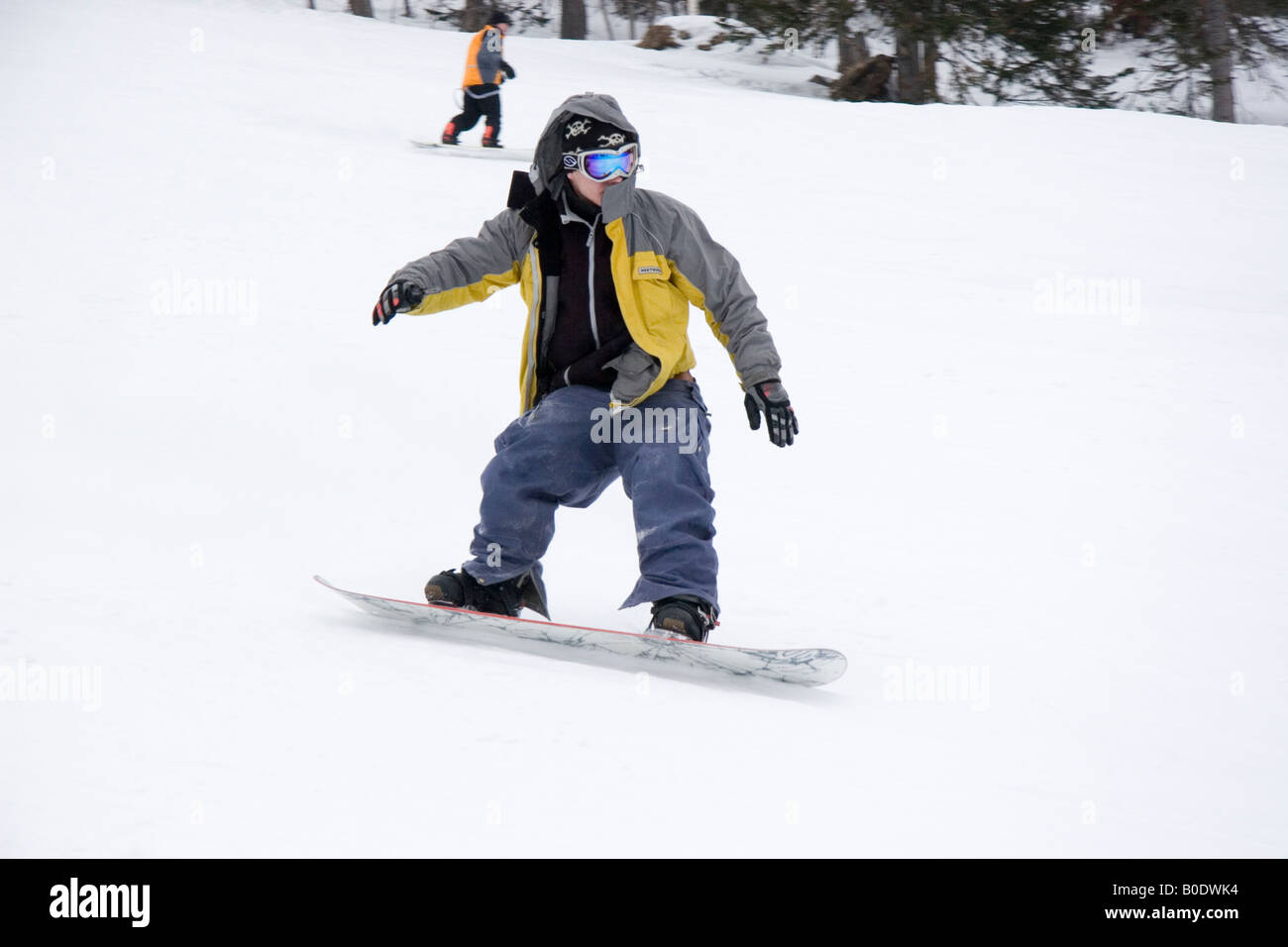 A young man on snowboard going down the hill in Sheregesh (Russia, Siberia) - Stock Image