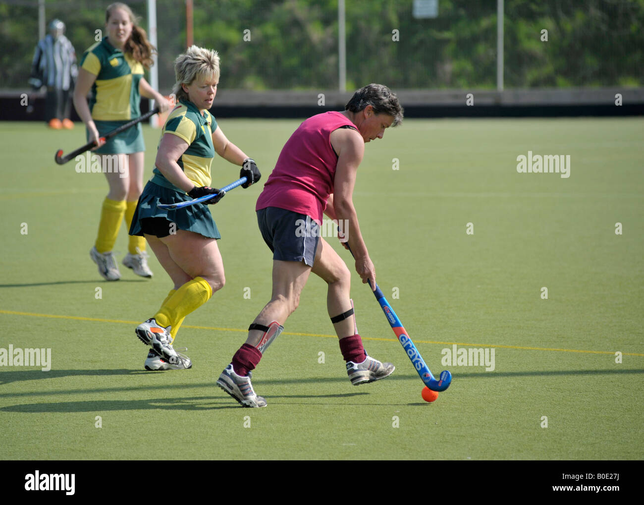 older women playing field hockey on astroturf outdoors stock photo