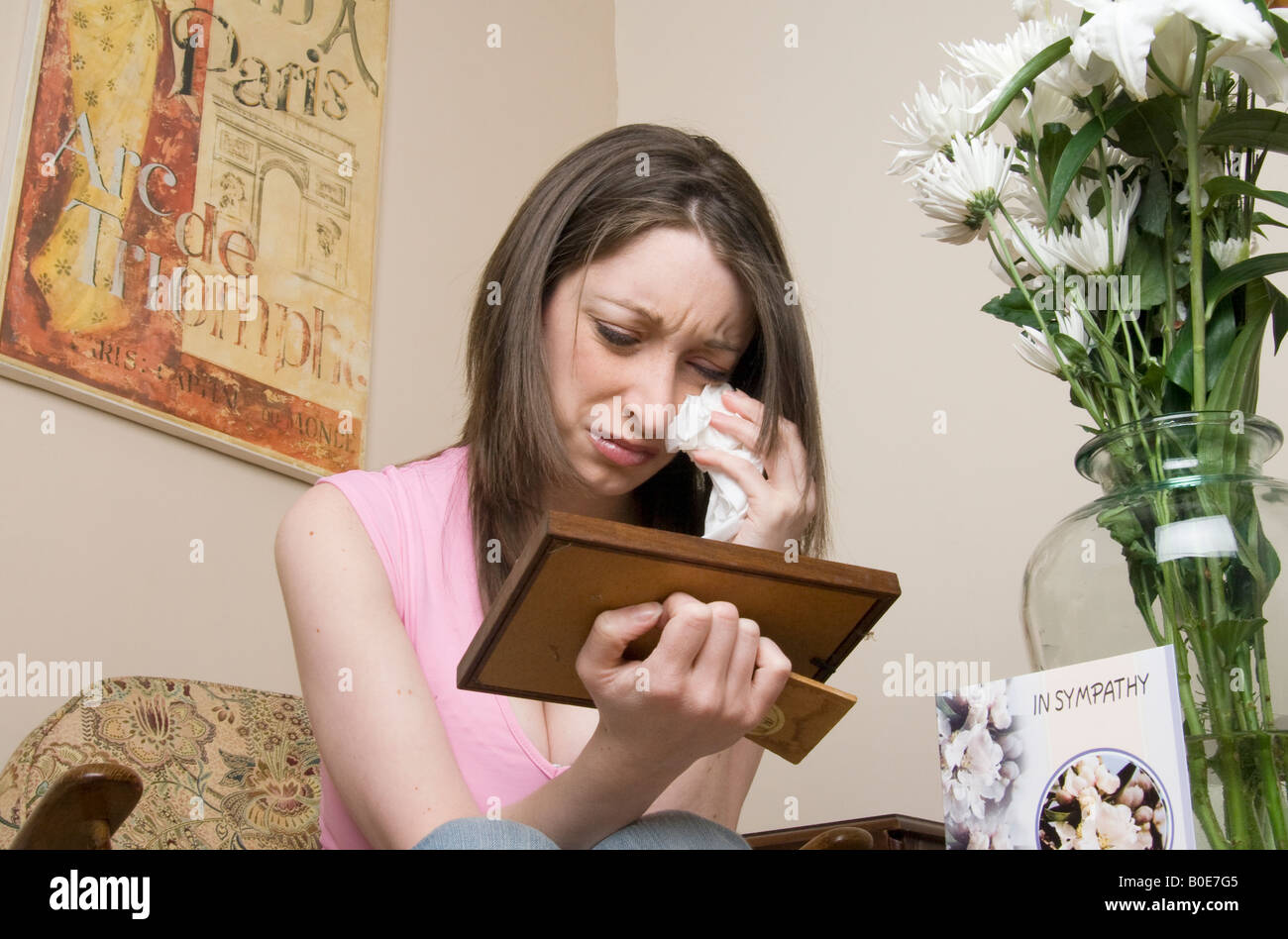 Young recently bereaved girl wiping away tears while looking at photo - Stock Image