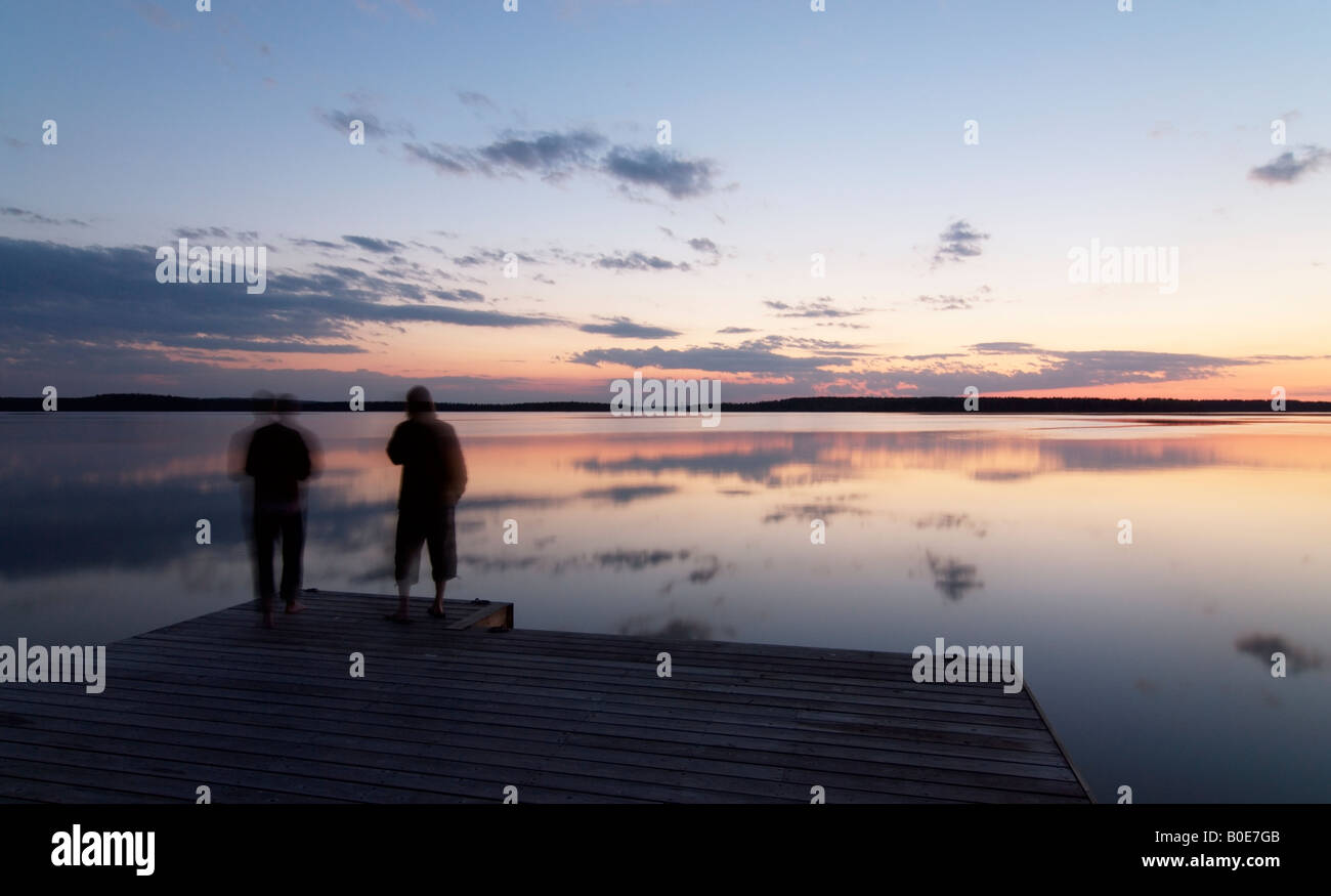 Two persons by calm lake Päijänne on quiet early summer night, Asikkala, Finland - Stock Image