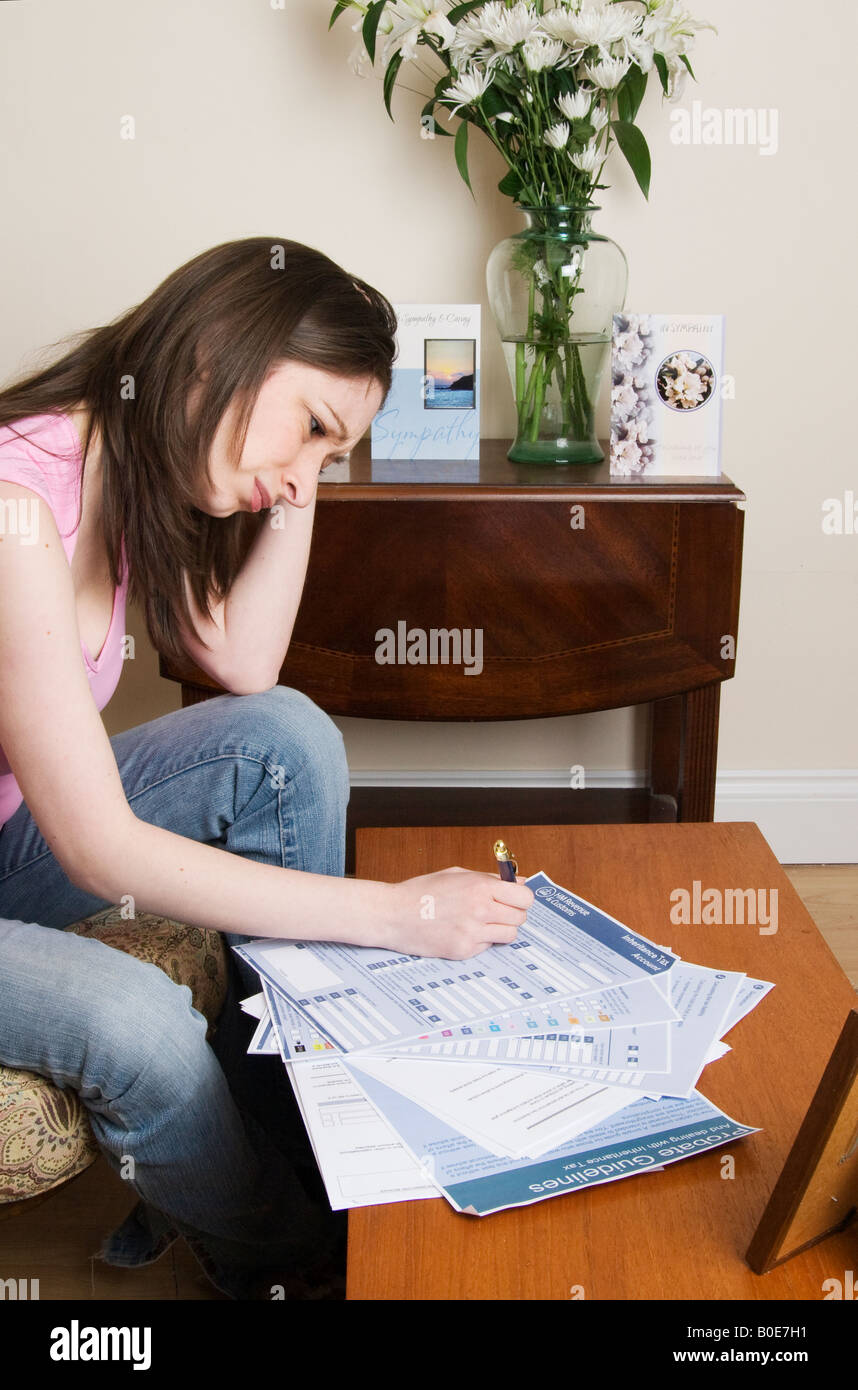 Widow or recently bereaved young woman completing probate forms - Stock Image