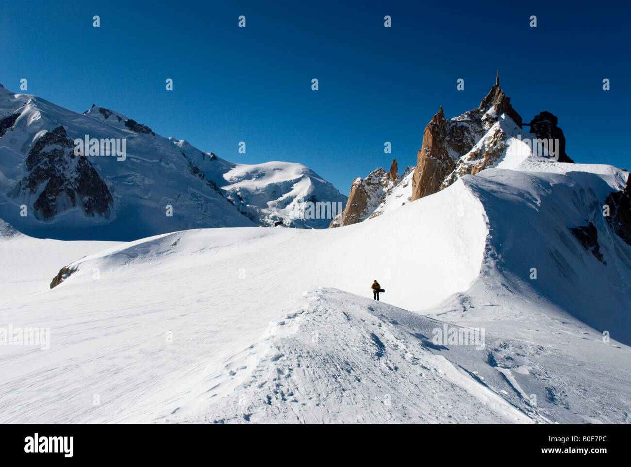 Snowboarder walking on ridge towards Grand Envers du Plan variant of Vallée Blanche, Aiguille du Midi in background - Stock Image