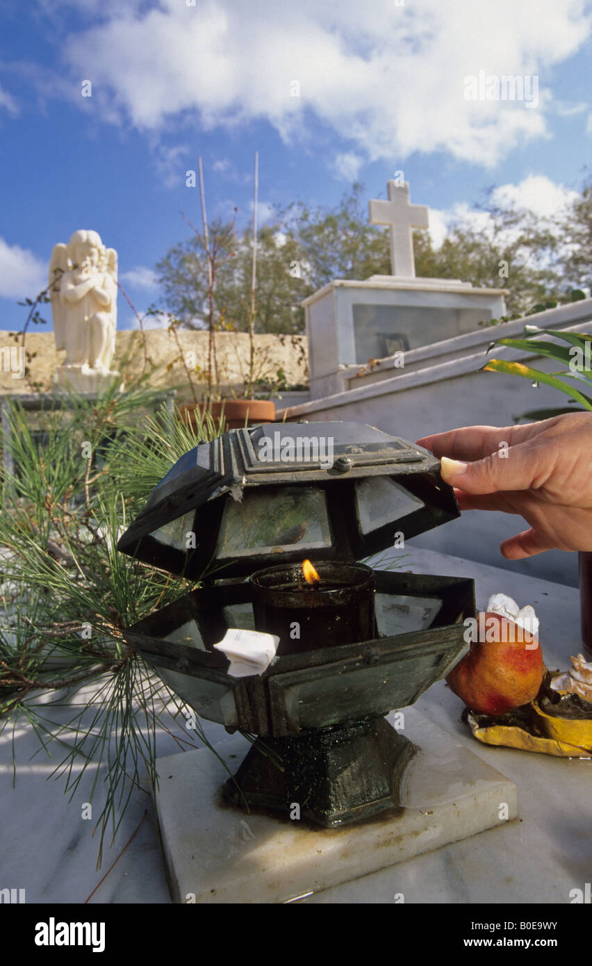 lighting an olive oil lamp on the grave of a deceased  near Iraklio on Crete - Stock Image