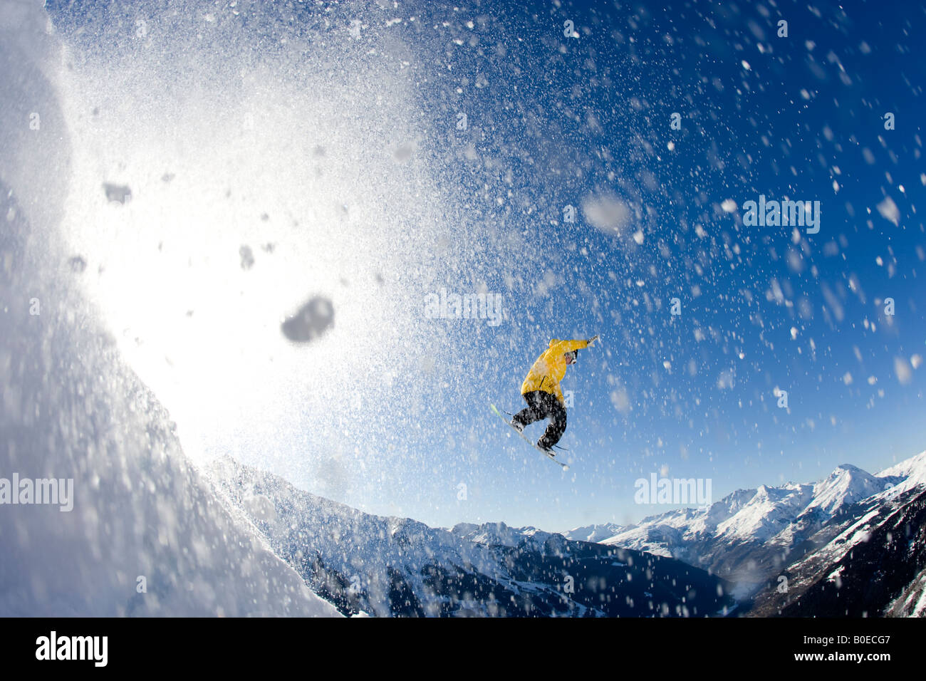 Snowboarder spins from a mountainside - Stock Image