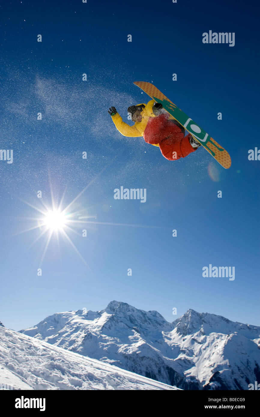Snowboarder flying over mountain peaks. - Stock Image