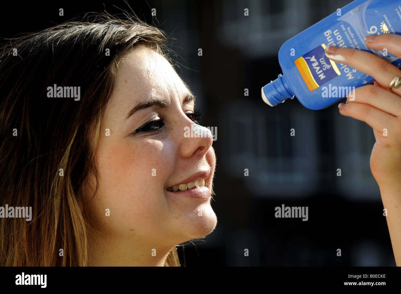 A teenage girl applies sun lotion to her face - Stock Image