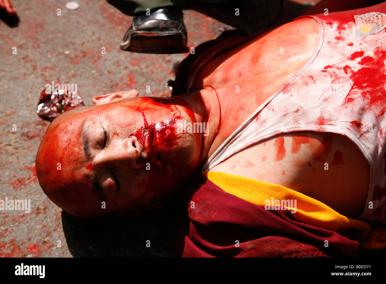 Tibetans re-enact scenes of the alleged recent Chinese brutality in Tibet. Fake blood is used by people playing - Stock Image