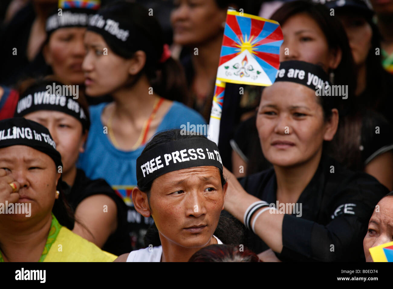 'Stop the Torture' and 'Free Press in Tibet' say the signs on the headbands of Tibetan protesters - Stock Image