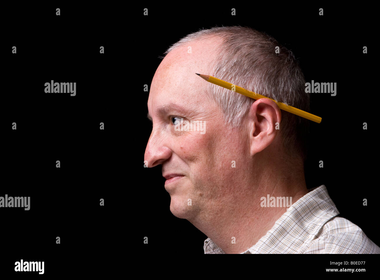 A mna with a pencil behind his ear, UK. - Stock Image