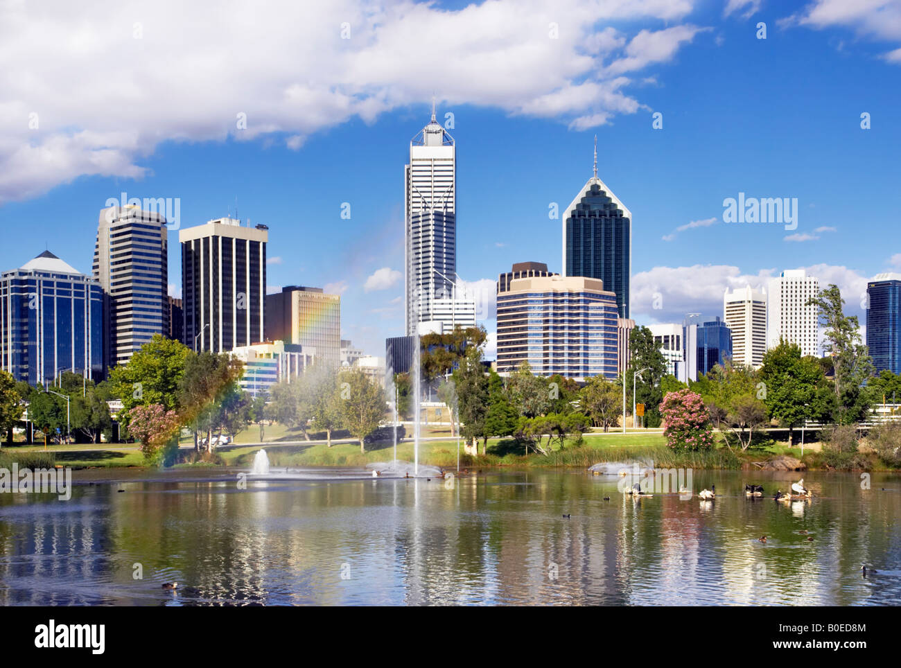 Perth's skyscrapers towering above an inner city park. A rainbow appears in the fountain's spray. Perth, - Stock Image