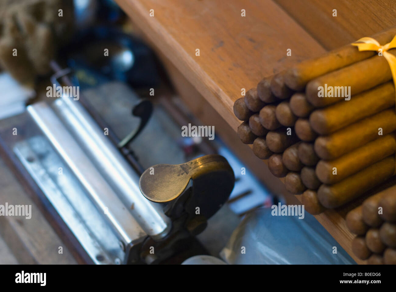 Hand made Cuban cigars stacked in a shop with a rolling machine Havana Cuba - Stock Image