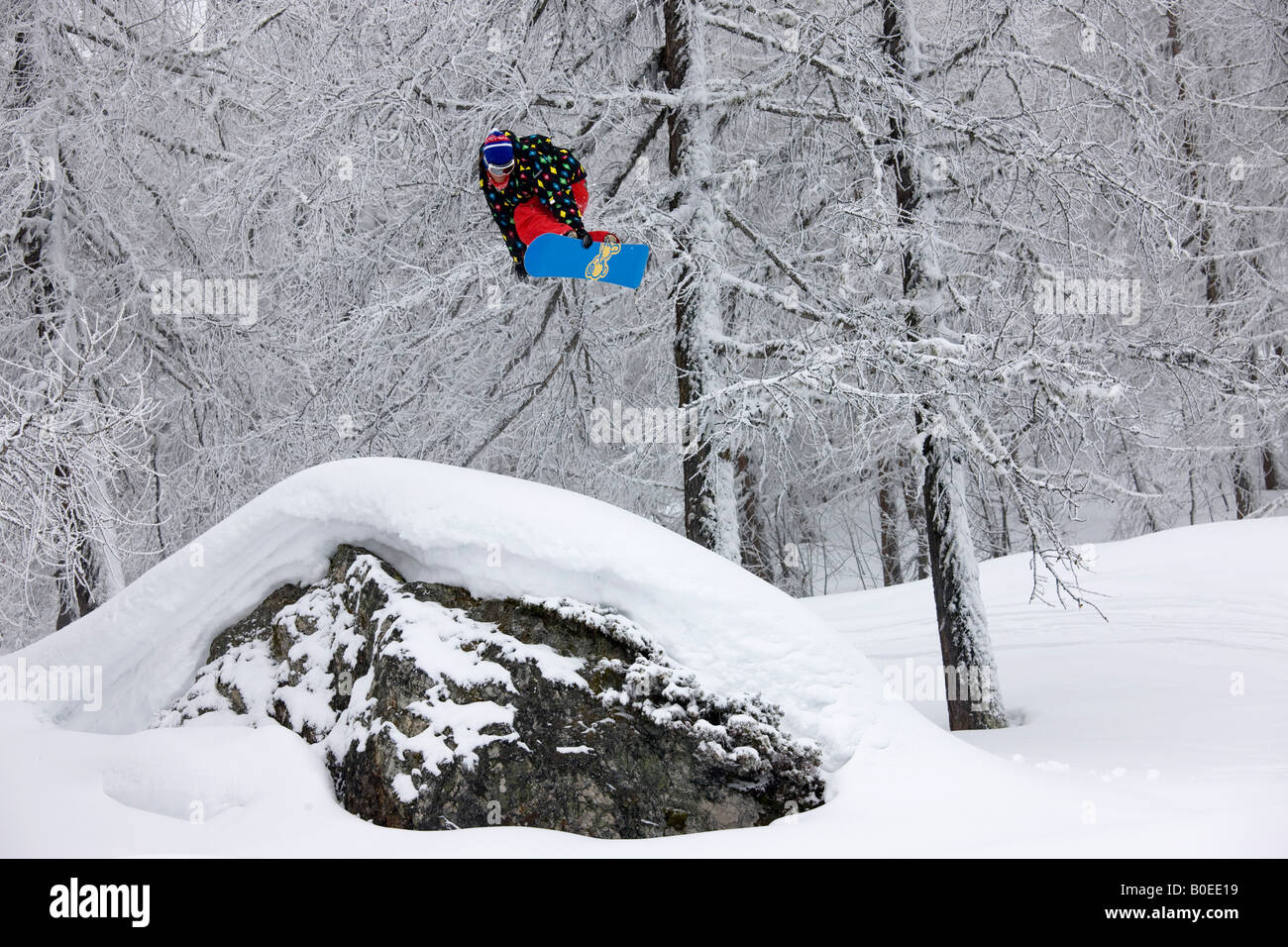 Snowboarder jumps from a rock off piste. - Stock Image