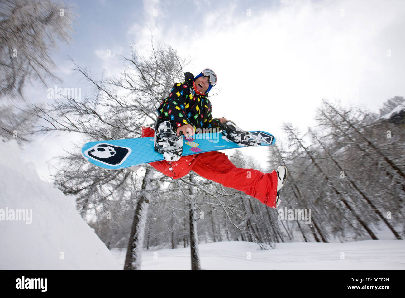 Snowboarder leaps from snow mound air guitar. - Stock Image
