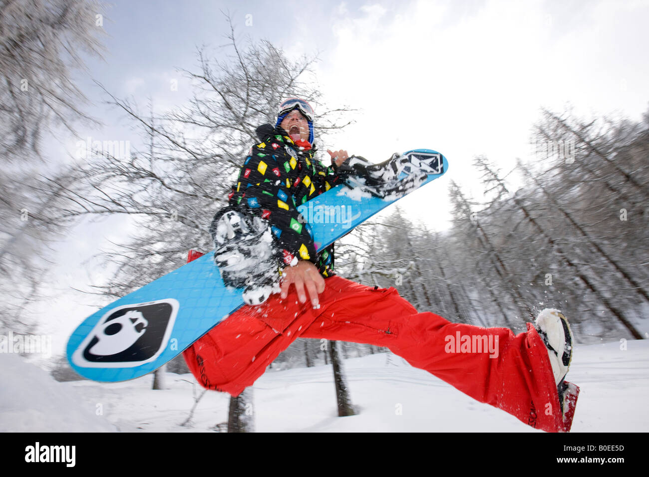Snowboarder running through the trees with snowboard having fun. - Stock Image