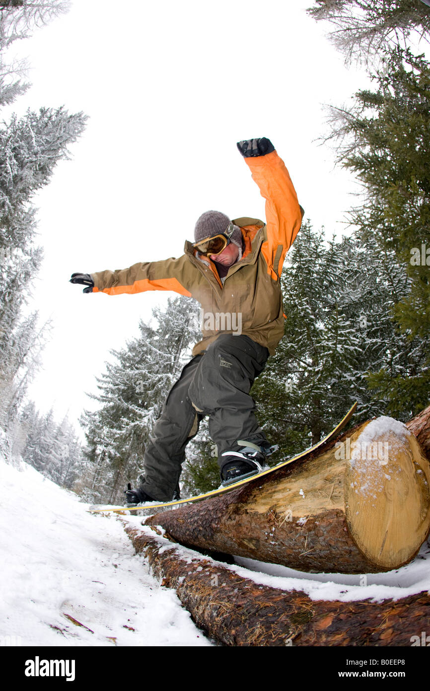 Snowboarder jibbing a log in the Alps Stock Photo