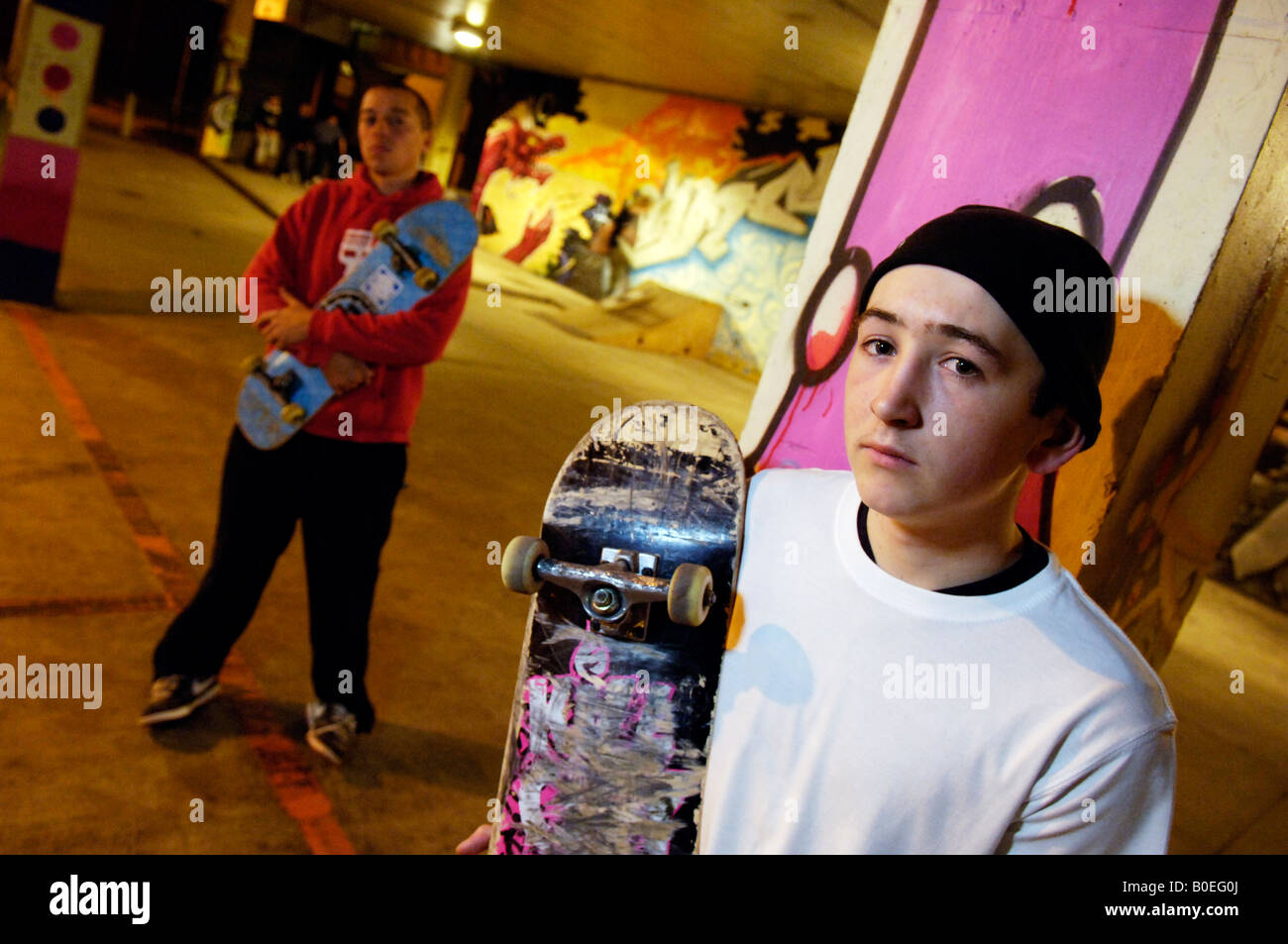 Young urban men youths boys at a skateboarding park during the night - Stock Image